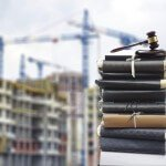 Stack of Books and Gavel on City Construction Background