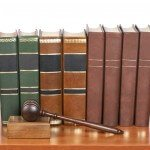 Wooden gavel from the court and old law books reflected on white background