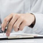 man hand with pen and business report on table