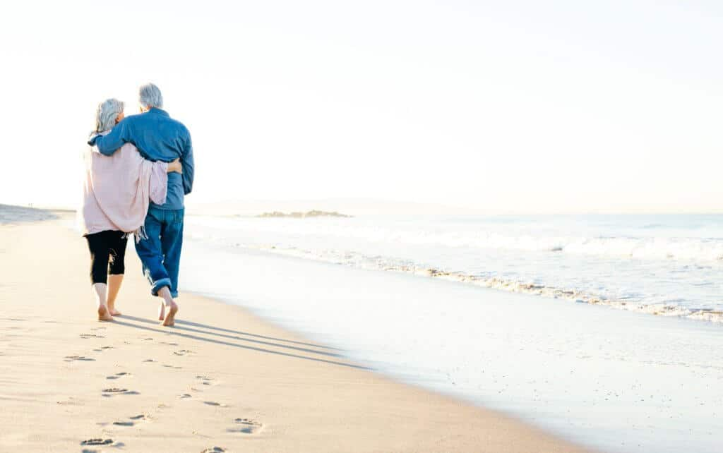 elder couple walking on beach